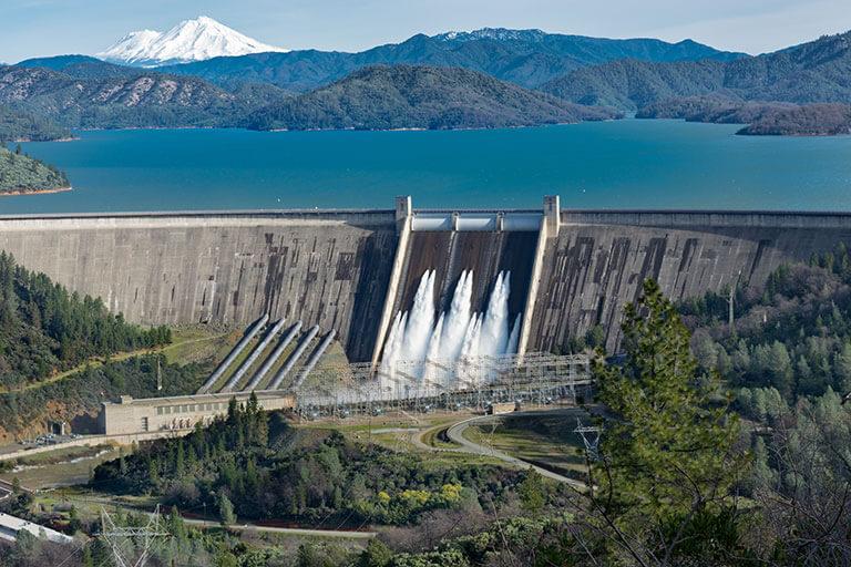 picture shasta dam surrounded by roads trees with lake mountains